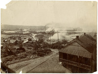 View from hill above of early facilities of Pacific American Fisheries in distance, Puget Sound Timber Company Mill on left, Earles and Cleary Shingle Mill in center
