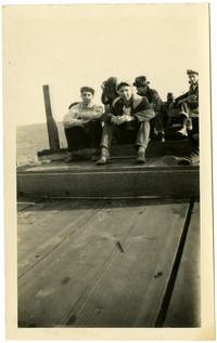 Several men sit on wooden platform, possibly a dock or ferry