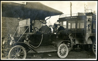 Two finely dressed women with hats sit in back of a 1915 Ford touring car, parked next to Bellingham train station