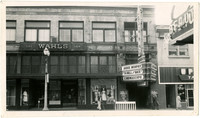 Store fronts on Holly Street include Wahl's Department Store, The Grand Theater, the Up and Up Tavern