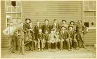 Twelve men and four boys pose outside a warehouse with broken windows