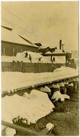 Several men shovel snowfall from roof of Pacific American Fisheries dockside structures