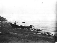 Unidentified person with a small motorboat at the water's edge