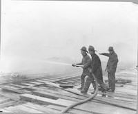Lumber Mill, Station #2 - three unidentified men standing on a plank roadway