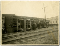 The underside of an upturned railcar with several men and boys standing next to it along railroad tracks