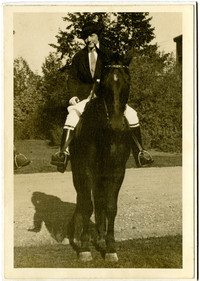 Woman in formal riding costume with jodhpurs, jacket, and boots sits atop horse