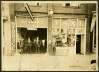 Four men stand in front of brick commercial building with storage service on left, Hale-Morton taxi service on right