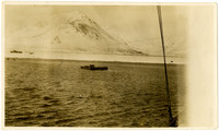 View from deck of ship of raft traveling towards shore with Pavlov Island volcanic mountains in distance