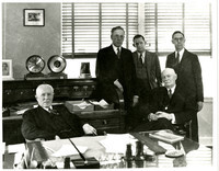 E.B. Deming, Arthur Deming (seated) with Bert Huntoon, Thad McGlinn, and D.M. Brosseau (standing) in business office