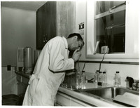 Man in labcoat conducts test in lab