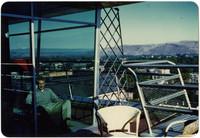 Man seated in windowed room atop tower in Eastern Washington