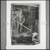 An unidentified man standing in front of stacks of wooden crates, holding a harpoon-like instrument