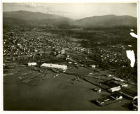 Aerial view looking east from Belingham Bay at Fairhaven, south Bellingham, with log booms at a lumber mill, and Pacific American Fisheries facilities at lower right