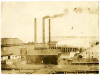 Cannery buildings on piers with three smokestacks and the Pacific American Fisheries insignia, and Bellingham Bay in background
