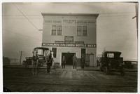 Storefront of Puget Sound Bottling Works in Fairhaven, WA, along wood-planked 11th street with early-model car and buggy with two horses parked in front