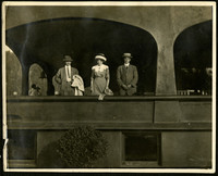 Two men and a woman, all well-dressed, stand in archway of large porch of sizeable building