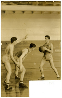 Three young men play basketball in gymnasium