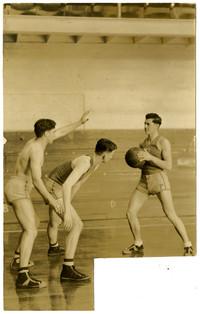 Three young men play basketball in gymnasium
