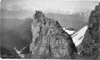 A large rocky outcrop with snow fields and mountains in the backgroun