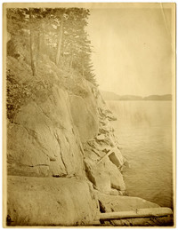 Trees perch on edge of steep rocky shoreline with waters of Chuckanut Bay seen on the right