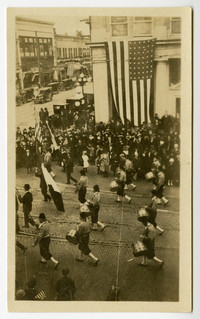 View from above of Armistice Day parade with drummers marching by crowd of onlookers in front of imposing, columned bulding with huge American flag
