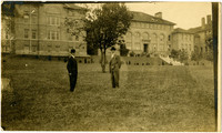Two men stand in front of Old Main on campus of Bellingham Normal School