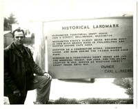 Unidentified man at sign for the site of the Territorial Court House in Bellingham, Washington (1308 E. Street)