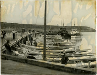Many small, single-masted fishing boats moored at pier, with three larger fishing boats