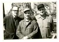 Three unidentified men, standing close to the camera with tall, rock outcrop behind them, possibly along Chuckanut Drive