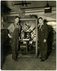 Ralph Erickson on right, Wes Randrup on left, standing next to tuna butchering machine encased in rectangular metal box