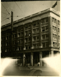 Exterior corner view of National Bank - large brick building with early-model car passing in front