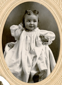 Baby dressed in long white gown, with dark curls