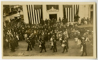 View from above of Armistice Day parade with drummers, sailors marching by crowd of onlookers in front of imposing, columned building with two huge American flags