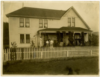 A group of six women and a couple stand on porch of two-story residence with picket fence