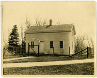 """Simple two-story wooden house called """"Stevens' House"""" set behind fence in Minnehaha Park"""