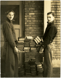 Young men carry load of books outside building
