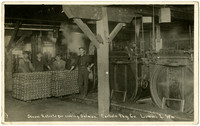 Four workers stand around two pallets of canned salmon inside cannery next to cooking vessels