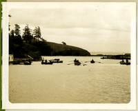 Several rowboats are rowed through a small straight with bluff on left, small docks on either side