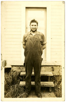 Young man in overalls stands outside a b