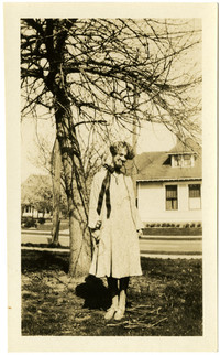 A young woman poses under a tree in a residential neigborhood