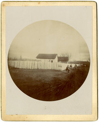 Circular photograph of three people walkign along fence with several buildings and field beyond