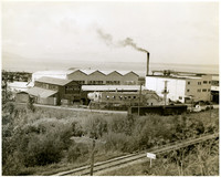 Warehouses and smokestack of industrial waterfront, Bellingham, WA, with Great Northern Rail Road tracks in foreground