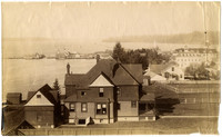 View of Roche Harbor, San Juan Island, over the rooftop of large home, with Hotel De Haro in upper right