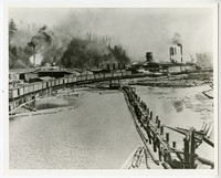 Lumber mill scene with railroad tracks elevated over water, with rail cars, running next to lumber mill with forested hills behind, possibly Samish Bay Mill