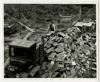 View from above of man cutting wood shakes next to huge pile of shakes and early model truck
