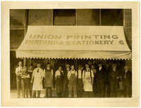 A group of men in suits or work aprons, and two women in slacks, stand under awning of Union Printing Binding & Stationary