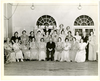 A seated man is surrounded by several rows of formally dressed women in a ballroom