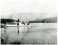 "Several people sit at prow of steam lauch ""Elsinore"" on Lake Whatcom, WA"