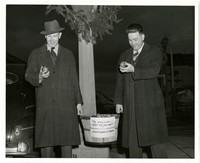 Two men in overcoats hold apples and apple basket