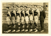 Seven uniformed members of young men's sports team and their coach pose outside building